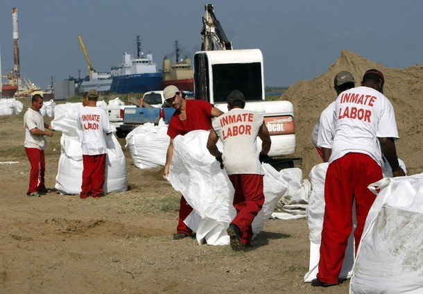 Inmates from a La Fourche parish jail on a work release program fill giant sandbags in Port Fourchon, Louisiana May 11, 2010. U.S. Army National Guard troops were dropping the sandbags using helicopters on nearby breaks in beaches to protect marshes from the BP oil spill offshore.   REUTERS/Rick Wilking (UNITED STATES - Tags: ENVIRONMENT DISASTER)