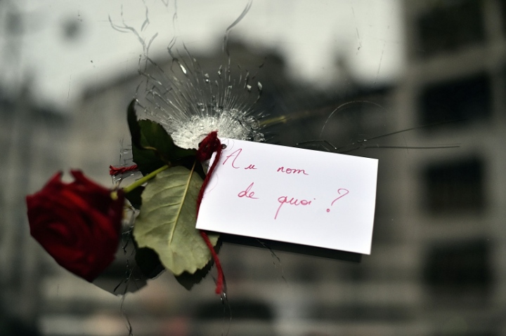 A rose with a sign reading 'In the name of what?' is pictured in a bullet hole in the window of a Japanese restaurant next to the cafe 'La Belle Equipe', Rue de Charonne, in Paris on November 14, 2015, following a series of coordinated attacks in and around Paris late on November 13. At least 128 people were killed in the Paris attacks on the evening of November 13, with 180 people injured, 80 of them seriously, police sources told AFP. AFP PHOTO / LOIC VENANCE (Photo credit should read LOIC VENANCE/AFP/Getty Images)