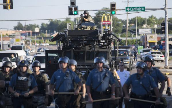 Riot police stand guard as demonstrators protest the shooting death of teenager Michael Brown in Ferguson, Missouri