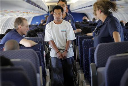 An illegal immigrant boards a plane at a flight operation unit at Mesa airport during his deportation process in Phoenix