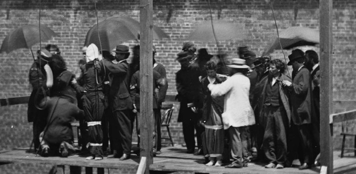 [Credit: Close-up of Lincoln conspirators prior to execution. Far left in the hood is the first woman to be executed by the US Federal Government/Alexander Gardner.]